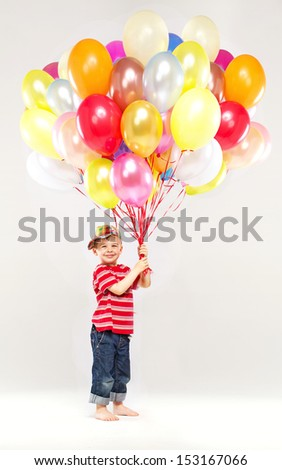 Small boy holding bunch of balloons - stock photo