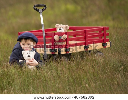 small boy holding his biege teddy bear with his red wooden wagon parked in the grass.