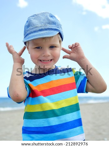 Small boy holds his hands over ears not to hear - stock photo