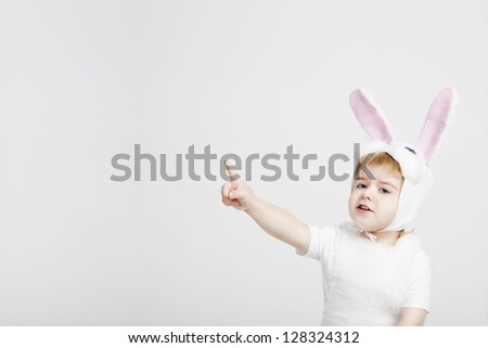 Small boy in a rabbit costume shows his finger to the side. Studio shot. Gray background - stock photo