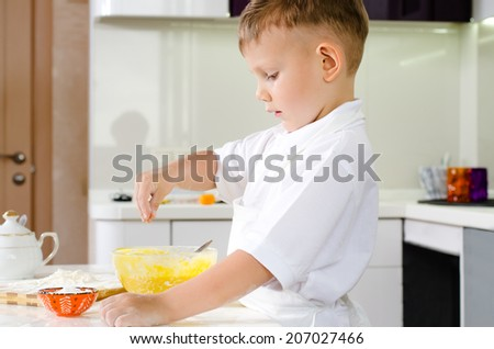 Small boy in a white apron standing baking in the kitchen breaking eggs into a mixing bowl for his batter, side view of him concentrating as he works - stock photo