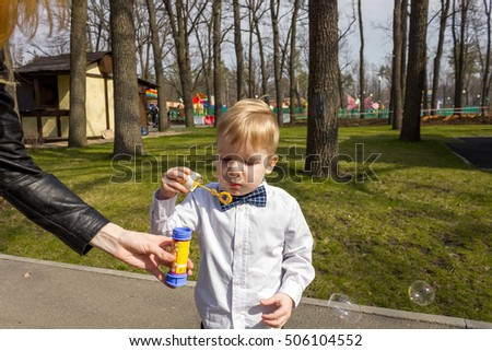 Small boy in shirt with bow tie  is playing with bubbles