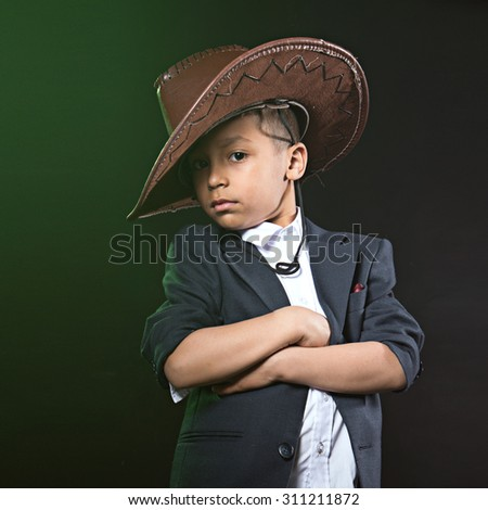 small boy in suit and cowboy leather hat stand with arms crossed at the black green background - stock photo