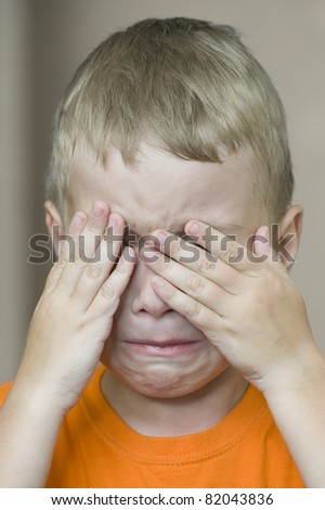 Small boy is covering his face by hands - stock photo