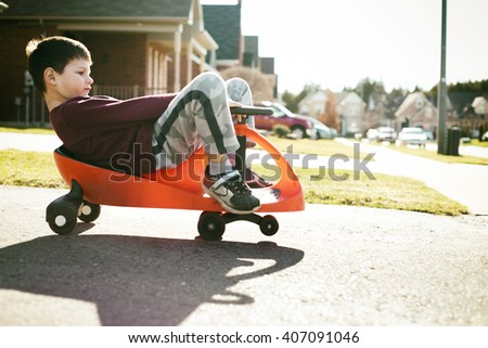 small boy is having fun riding his toy on the street - stock photo