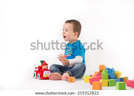 Small boy is playing with colorful cubes - stock photo
