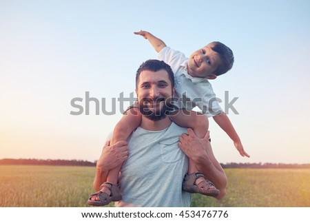 Small boy is sitting on his father's shoulders and pretending a plane during walk in the field - stock photo