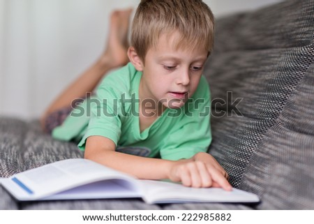 Small boy lying on a sofa reading a big book concentrating carefully following the text with his finger - stock photo