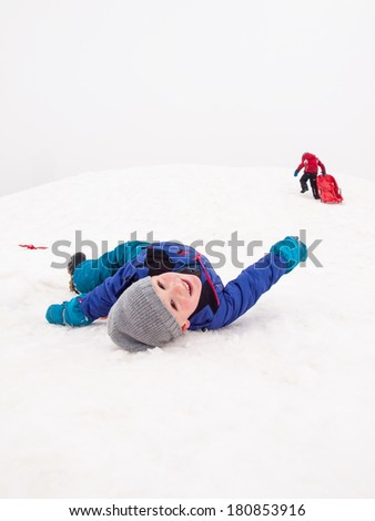 small boy lying smiling on snow at teh bottom of a sledging hill - stock photo