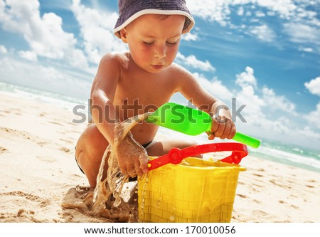 Small boy playing with toys on the sand beach  - stock photo