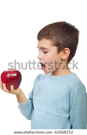 Small boy preparing to bite a big red apple and standing in semi profile isolated on white background - stock photo