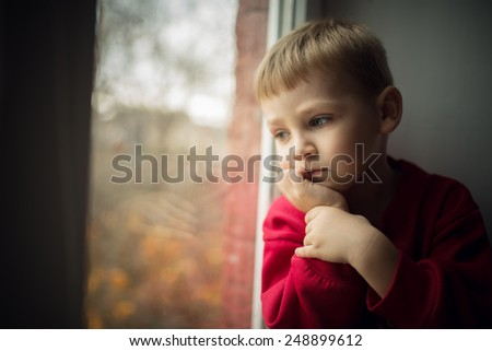 small boy sitting near window and thinking about something