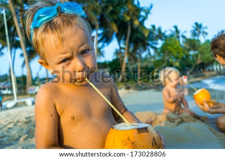 Small boy sitting on the beach and drinking coconut milk - stock photo