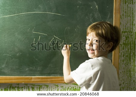 Small boy smiling as he writes on a chalkboard. Horizontally framed photo. - stock photo