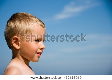 Small boy smiling on a beach in a sunny day - stock photo