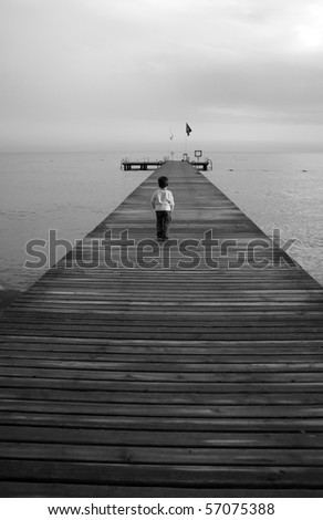 Small boy standing on a pier, black white
