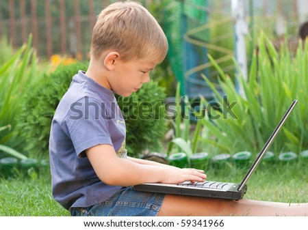 Small boy using notebook outdoor - stock photo