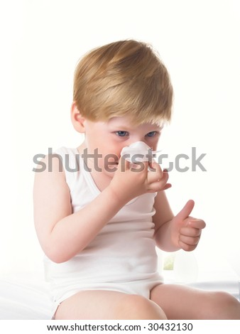 Small boy wipes a nose a napkin