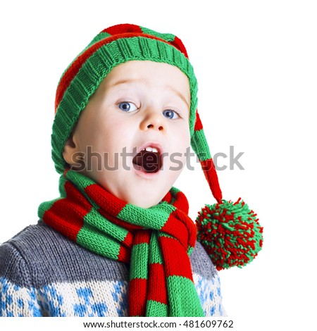 Small boy with blue eyes in knitted hat, scarf and sweater sings a Christmas song. Isolated on white background.