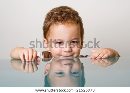 Small boy with curly hair behind glass table - stock photo