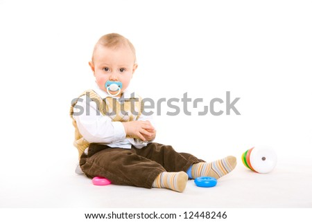 small boy with pacifier plays on the floor - stock photo
