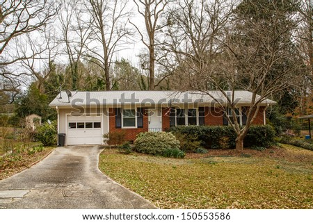 Small brick bungalow with white garage and satellite dishes on roof - stock photo