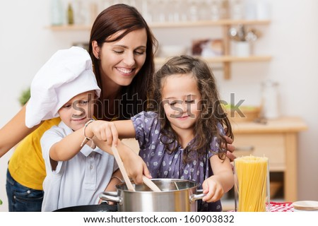 Small brother and sister cooking a meal both stirring the contents of the same pot watched over by their laughing young mother - stock photo