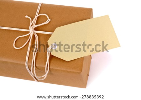 Small brown parcel package, manila label, isolated, copy space - stock photo