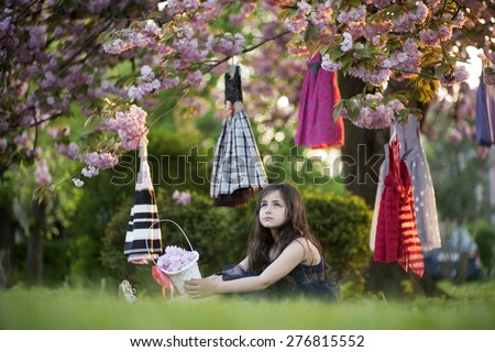 Small brunette girl with basket looking away sitting in the garden among colorful baby dresses hanging in the japanese cherry blossom tree, horizontal picture - stock photo