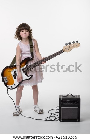 Small brunette is playing the bass guitar with funny face. Kid looks not in the camera. Full body shot. Expensive musical instrument and its amp. - stock photo