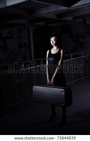 Small brunette lady holding big suitcase in the dark airport terminal - stock photo