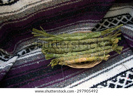 Small bundles of traditionally rolled and tied tobacco leaves in wicker basket on mexican blanket. - stock photo