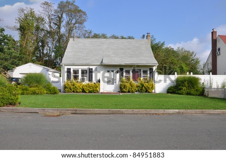 Small Bungalow Cottage Style Suburban Home on Sunny Day in Residential Neighborhood - stock photo