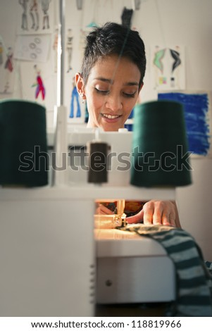 Small business and self-employed women, young hispanic woman working as fashion designer with sewing machine in studio - stock photo