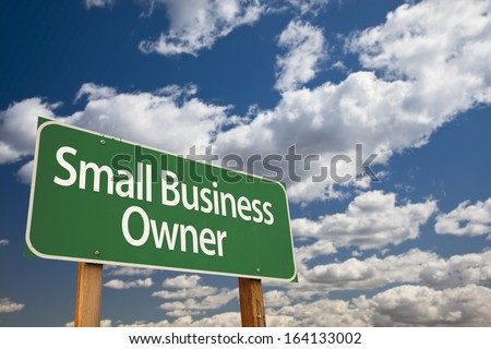 Small Business Owner Green Road Sign with Dramatic Clouds and Sky. - stock photo