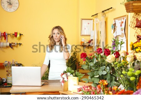 Small business owner. Portrait of mature florist standing at her flower shop behind the computer and making call. - stock photo