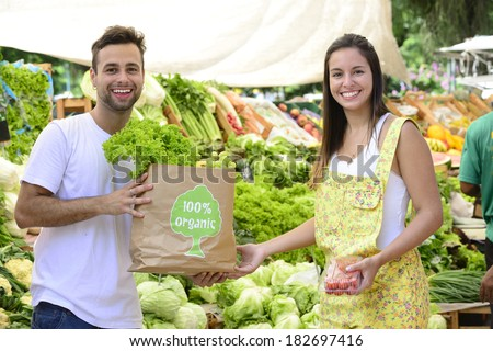 Small business owner selling organic fruits and vegetables to a woman carrying a shopping paper bag with a 100% organic certified label. - stock photo