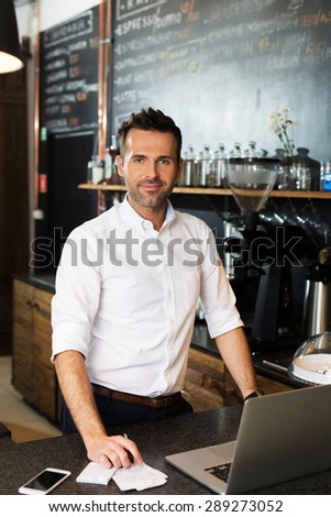Small business owner working at his cafe - stock photo