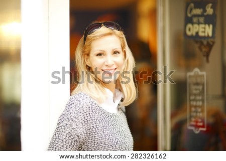 Small business. Portrait of confident female owner standing with arms crossed at shop facade.