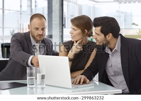 Small businessteam working together, using laptop computer, sitting at table. - stock photo