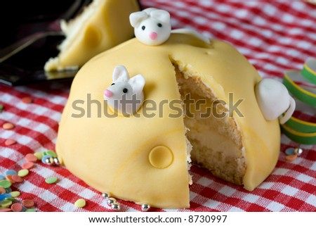 Small cake decorated as a cheese with little white mice on it