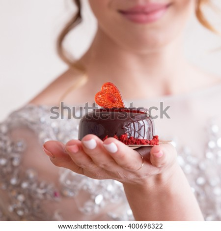 small cake of chocolate jelly with red sugar hearts on a palm