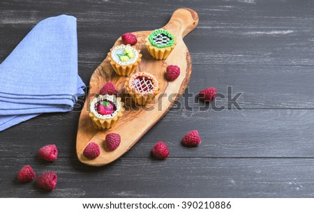 Small cakes petit fours in the form of baskets with cream and jam on a wooden plank from a tree of olive, blue cloth, worn on a dark black background in rustic style, Empty place for text - stock photo