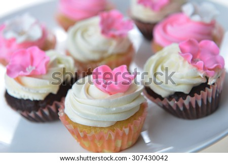 Small cakes with sweet icing on white background