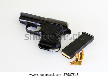 Small .25 caliber automatic handgun on neutral background with clip and bullets.