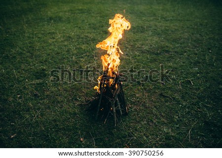 Small campfire on green meadow - stock photo