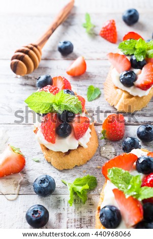 Small canape, crostini with grilled baguette with cream cheese, blueberry, strawberry, honey and mint on old white wooden background. Delicious appetizer or dessert. - stock photo