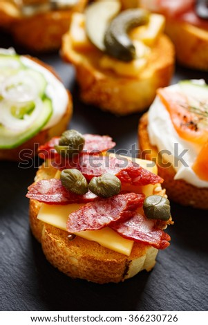 Small canape with grilled baguette with the addition of sausage, capers on  stone black background - stock photo