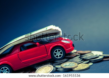 Small car carrying many dollars, blue background - stock photo