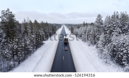 Small car driving next to semitrailer truck on winter asphalt road. The Kola route is in northern part of Karelia, Russia. Aerial view from drone
